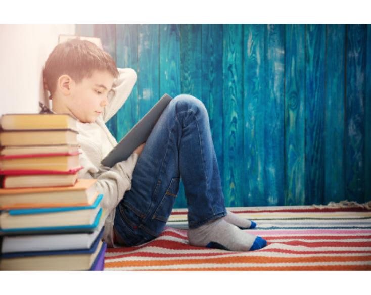 Enfant lisant assis dos au mur